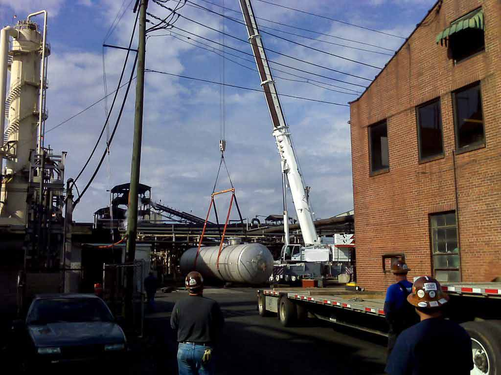 Crane lifting large tank
