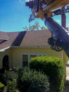 Crane lifting over house