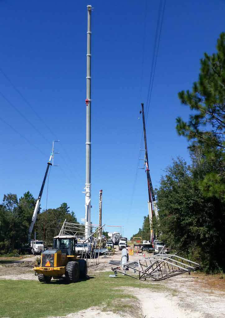 Crane placing high electric pole